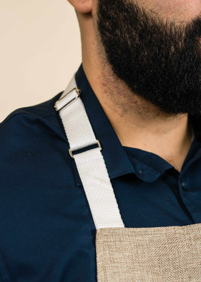 closeup of a white apron strap on a man's shoulder, including part of the apron and the man's bearded face