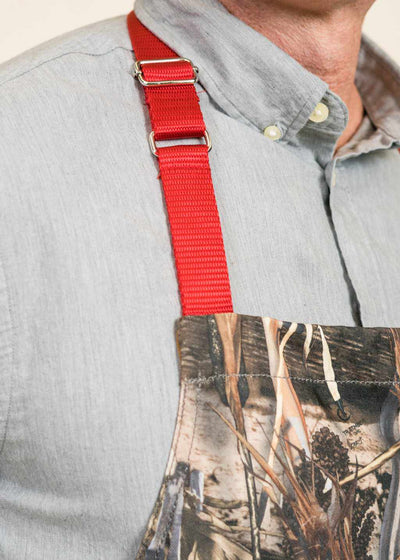 Closeup of the shoulder strap of a camoflauge apron with red strap, on a man wearing a gray-blue shirt