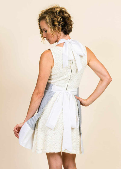 blonde woman wearing a white dress, with her back to the camera.  The corner of her white seersucker apron with white ruffle is visible