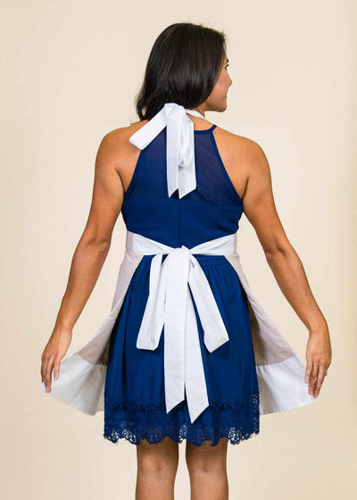 Brunette woman with back to the camera wearing a blue dress and an apron with thick white straps