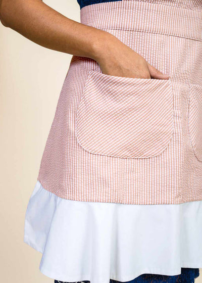 closeup of a wrist with a hand sticking in the hip pocket of a red and white apron