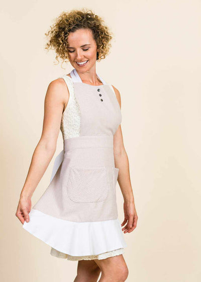 blonde lady twirling in a tan and white seersucker apron