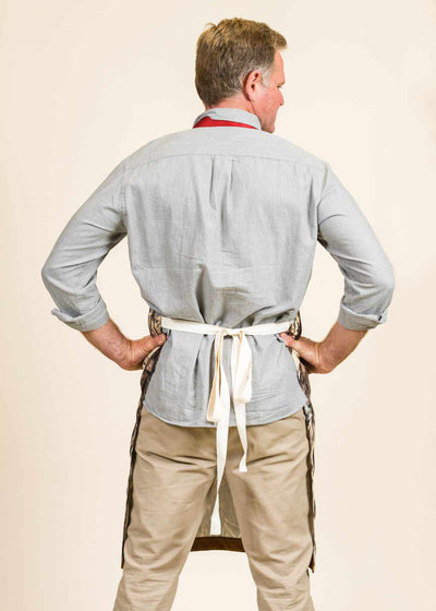 The backside of a man wearing a blue shirt, khaki pants, and apron with white straps around his back.