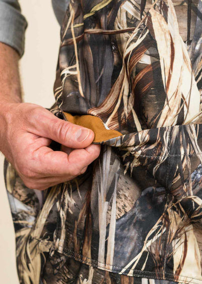 closeup of a hand showing the interior lining of a pocket on a camo apron