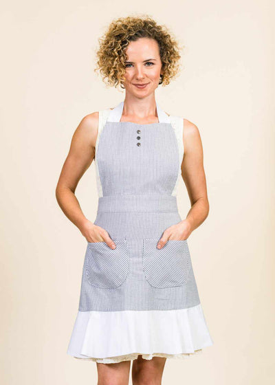 Proudly wearing her black and white seersucker apron with white ruffle, an attractive woman faces the camera