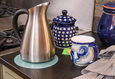 silicone trivet being used under hot tea pot