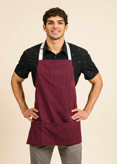 Athletic young man wearing a dark shirt, red apron with white stripes and white straps, and smiling at the camera
