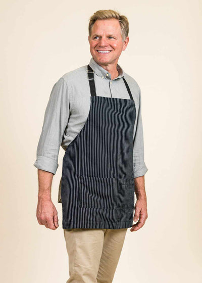 side front view of smiling man wearing a black apron with white stripes and a light blue shirt. The man is blond