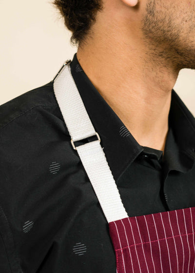 closeup of a white apron strap on a man's shoulder, showing the corner of the apron and the man's neck with stubble