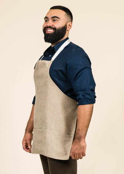 profile shot of large man with beard wearing a blue shirt and a sawgrass fabric apron with white stripes