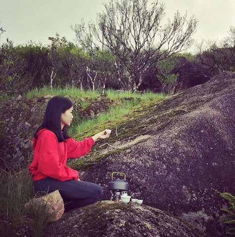 A young woman sits on a rocky outcrop with a cup of tea