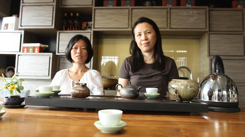 Two tea masters sit in front of a table with teaware