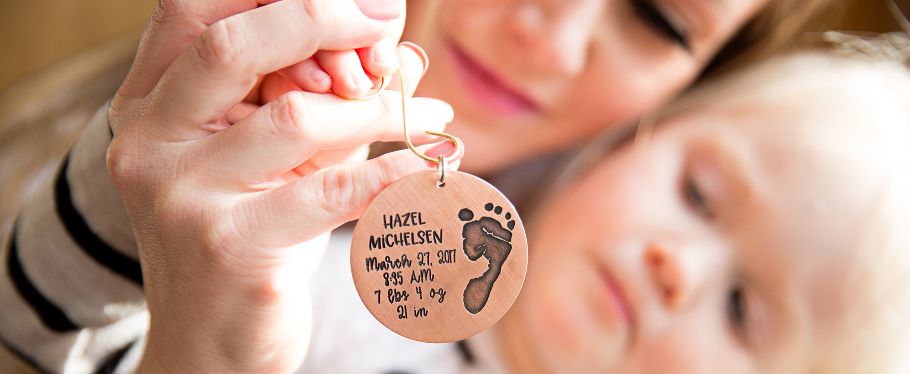Mom and baby daughter holding a personalized ornament engraved with baby's footprint and baby's birth stats.