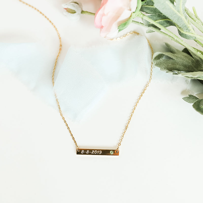 Gold bar necklace personalized with engraved name and birthstone shown on light background