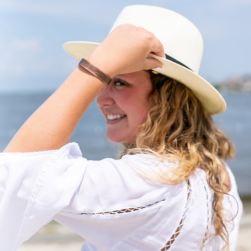 Young woman wearing oxidized copper bracelet personalized with GPS coordinates. She appears to be on a beach and is holding a rim of her sun hat.