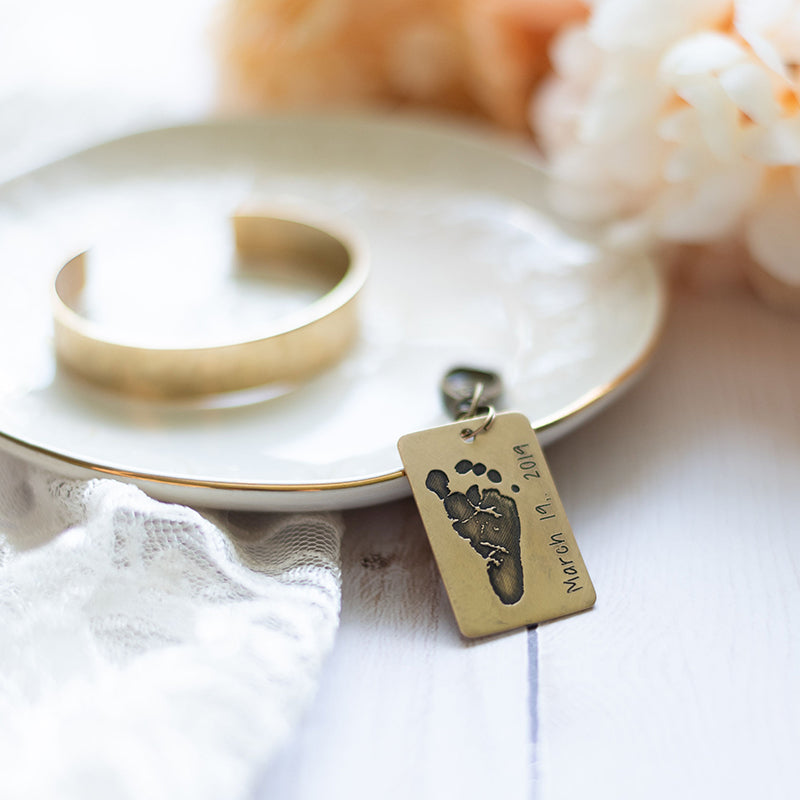 Key chain personalized with baby's footprint propped on a jewelry dish. A hammered gold color personalized bracelet is laying on the dish