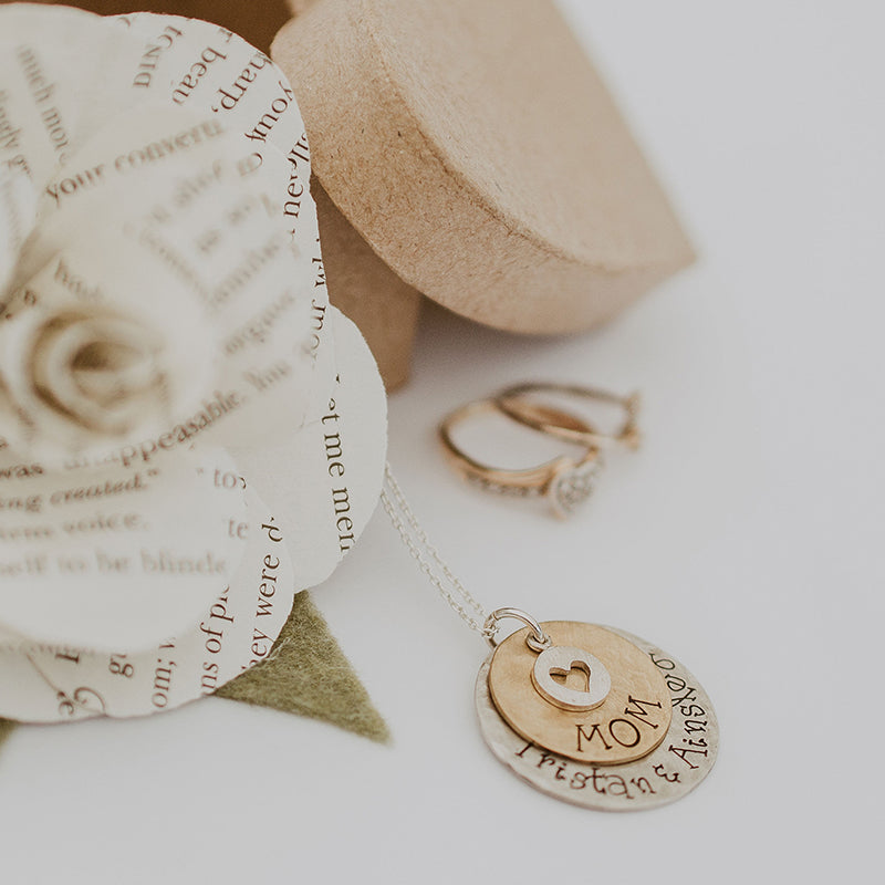 "Sterling silver and gold layered necklace with silver heart cut out charm. Top, gold disc is engraved with word ""Mom"" and bottom with names.  Shown on light background that includes paper flower and gift box"