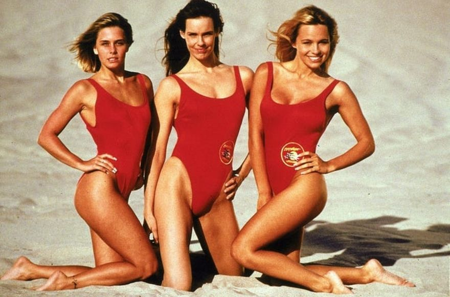 Baywatch cast members in red swimsuits on beach