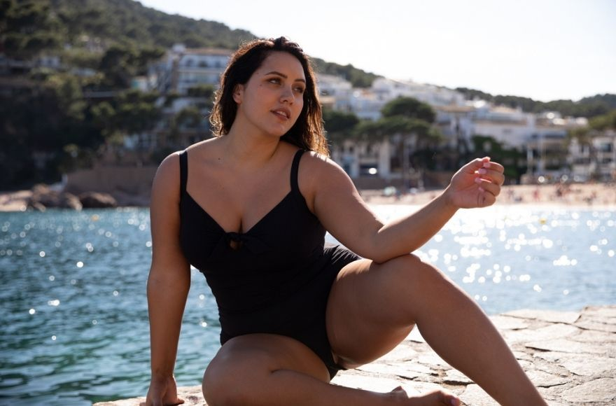 Woman wearing plus size black swimsuit