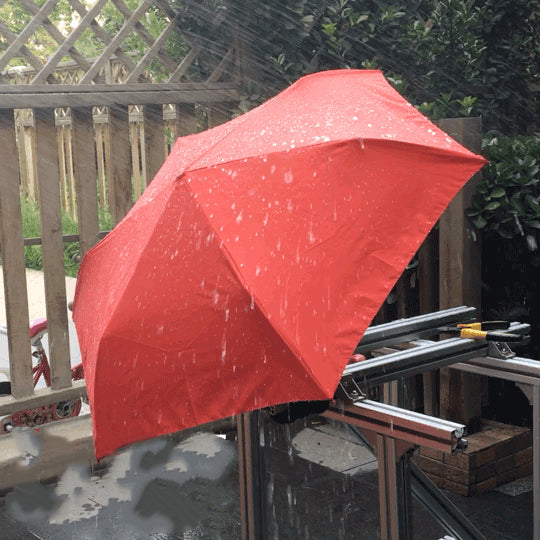 water spray a red umbrella to test its rain protection ability