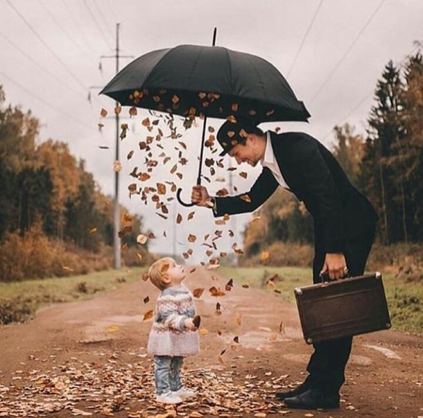 Daddy doing a magic for little boy with an umbrella