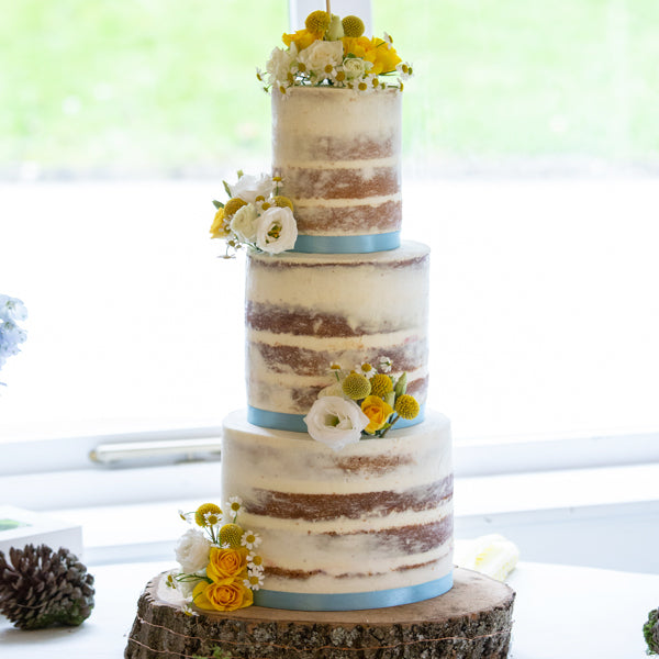 Joanne and Ross' semi naked wedding cake with white and yellow flowers
