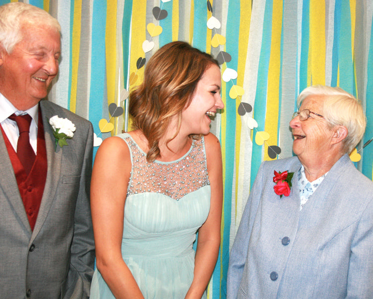Grandad, Natasha and Nanny in the homemade yellow, blue and grey photobooth