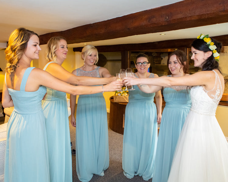 Bridesmaids in duck egg blue dresses all holding prosecco and the bride on the right