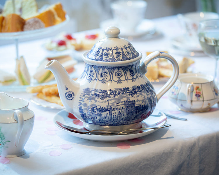 The tea pot and cakes from my mums tea party. Set on a white table cloth with a blue and white tea pot.