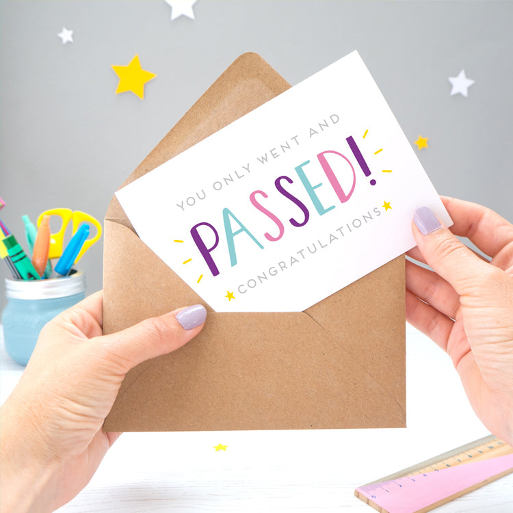 An exam congratulations card that reads 'You only went and passed! Congratulations' The image has a grey background with white and yellow stars, whilst two hands remove the card from the envelope.