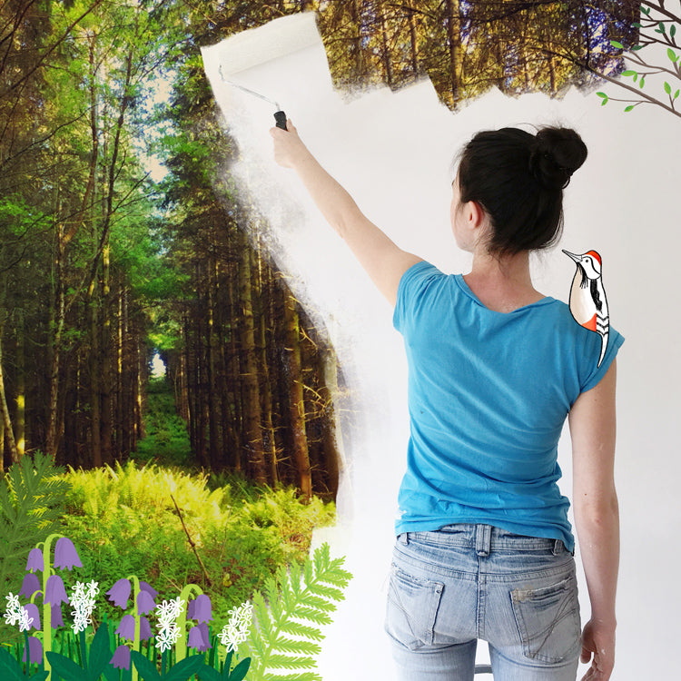 Joanne painting a wall with a forest background, illustrated flowers and with a bird sat on her shoulder.