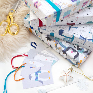 A stack of presents wrapped in my Llama, Polar Bear, Arctic Fox and Penguin wrapping paper. All four matching tags are laid out alongside the gift wrap.