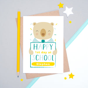 A happy 1st day at school personalised card featuring a friendly bear sat on a grey and white background.
