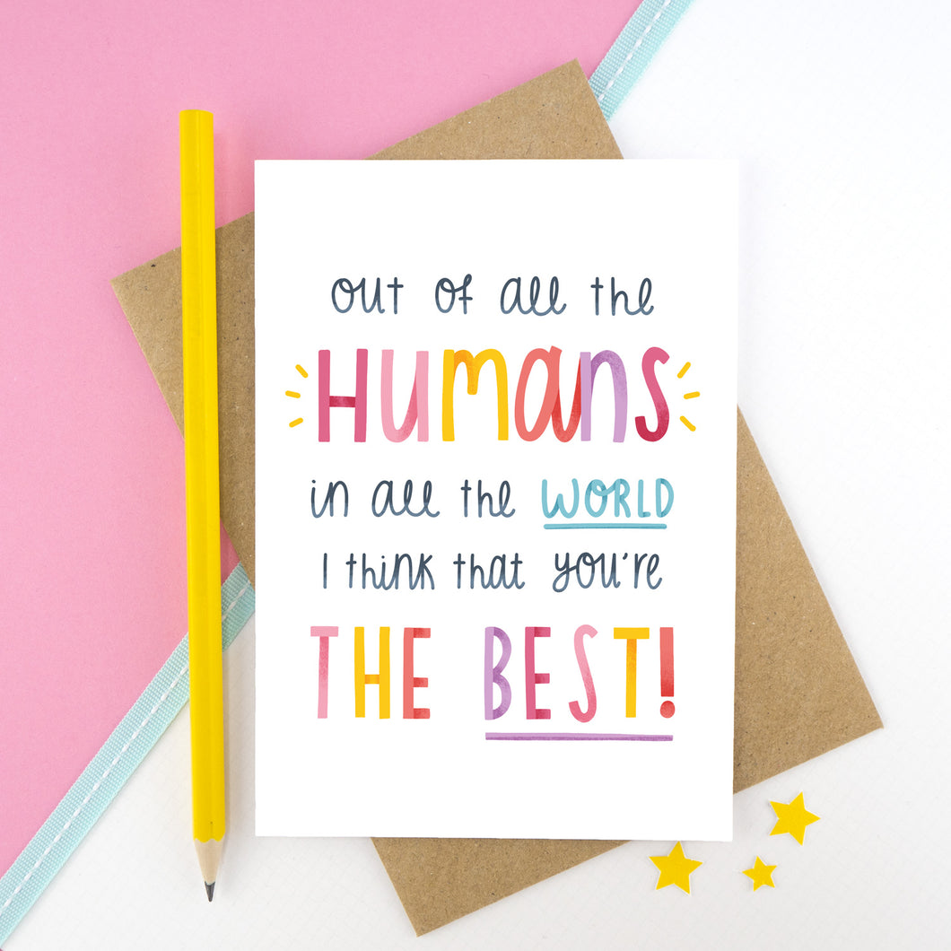 'Out of all the humans in all the world I think that you're the best!' card photographed on a white and pink background with a blue ribbon stripe. There is a yellow pencil to the left and small yellow stars at the bottom.