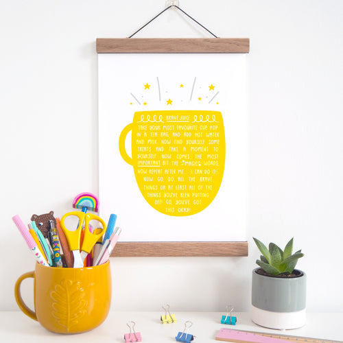 Brave juice print featuring a yellow cup of tea, which is hung on a solid oak magnetic frame.