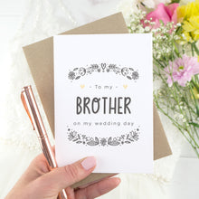 To my brother on my wedding day. A white card with grey hand drawn lettering, and a grey floral border. The image features a wedding dress and bouquet of flowers.