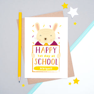 A happy 1st day at school personalised card featuring a friendly rabbit sat on a grey and white background.