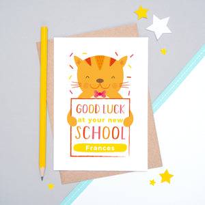 A good luck at your new school personalised card featuring an orange friendly cat sat on a grey and white background.