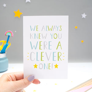 We always knew you were a clever one card held by Joanne Hawker over a grey background with white and yellow stars. The typography is in shades of green, grey and blue with two yellow stars.