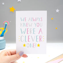 Load image into Gallery viewer, We always knew you were a clever one card held by Joanne Hawker over a grey background with white and yellow stars. The typography is in shades of pink, grey and blue with two yellow stars.