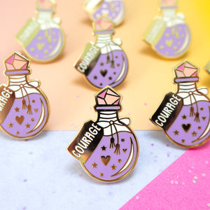 A potion bottle filled with an elixir of purple courage mixed with hearts and stars with a crystal topper in the form of an enamel pin.