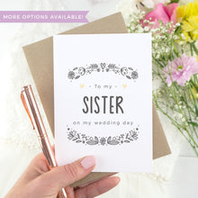 Load image into Gallery viewer, To my sister on my wedding day. A white card with grey hand drawn lettering, and a grey floral border. The image features a wedding dress and bouquet of flowers.