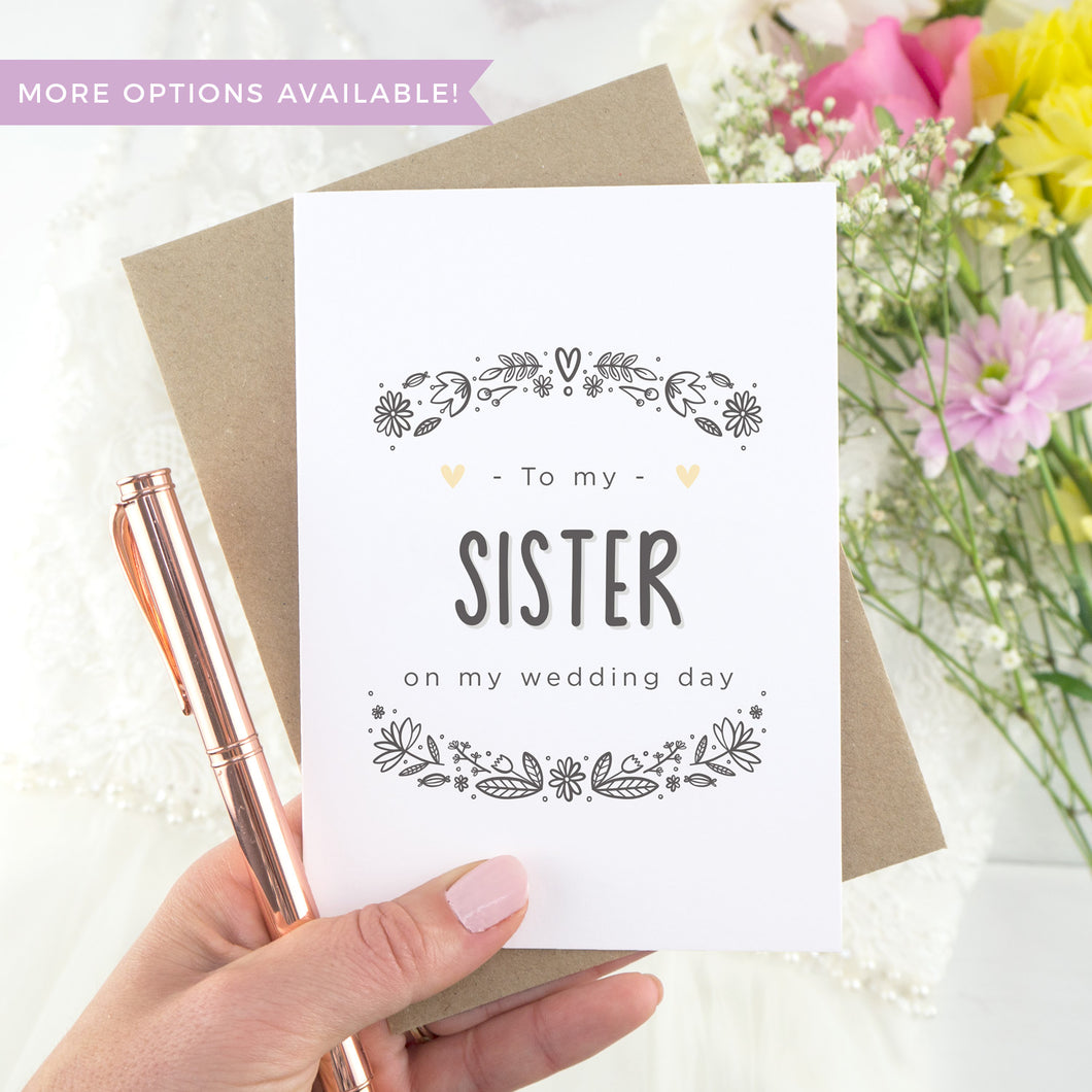 To my sister on my wedding day. A white card with grey hand drawn lettering, and a grey floral border. The image features a wedding dress and bouquet of flowers.