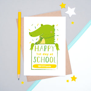 A happy 1st day at school personalised card featuring a friendly green crocodile sat on a grey and white background.