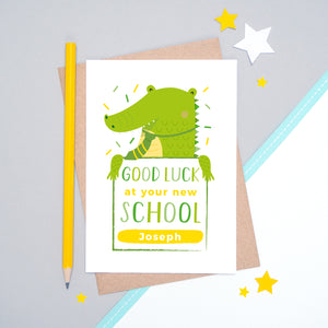 A good luck at your new school personalised card featuring a green friendly crocodile sat on a grey and white background.
