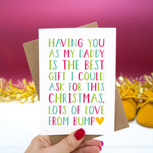 "Load image into Gallery viewer, Having you as my Daddy is the best gift I could ask for this Christmas, lots of love from bump."" - Christmas bump card with red and green text set on a red background with gold tinsel and mustard shoes."
