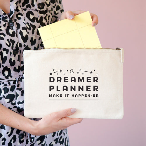 Dreamer and planner large accessory pouch in natural being held with a notebook being pulled out of it.