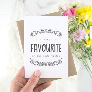 To my favourite on our wedding day. A white card with grey hand drawn lettering, and a grey floral border. The image features a wedding dress and bouquet of flowers.