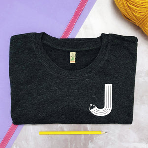 Grey charcoal tshirt with a white letter pencil initial J, flatlay.