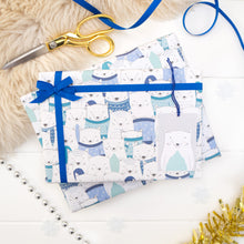 Load image into Gallery viewer, A parade of arctic foxes wearing a variety of woolly jumpers printed onto white gift wrap. Matching fox tag shown on the bottom right of the wrapping paper. The present is strung with blue ribbon and features a small bow.